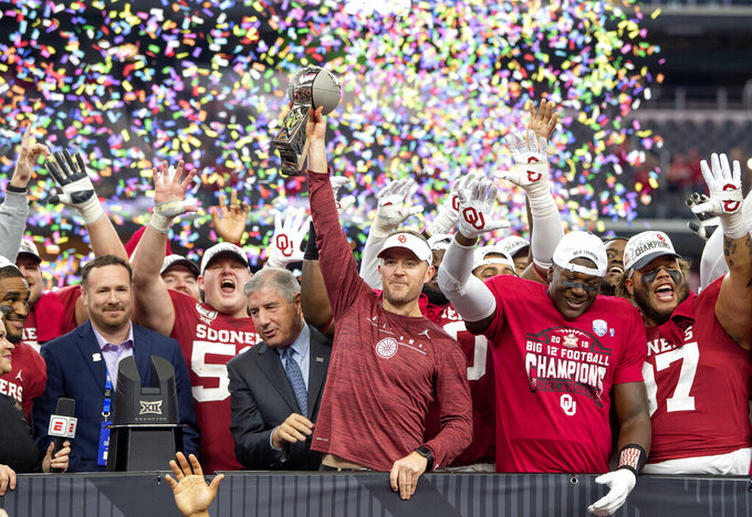 Oklahoma head coach Lincoln Riley hosts the Big 12 Conference championship trophy after defeating Baylor 30-23 in overtime in an NCAA college football game, Saturday, Dec. 7, 2019, in Arlington, Texas. (AP Photo/Jeffrey McWhorter)