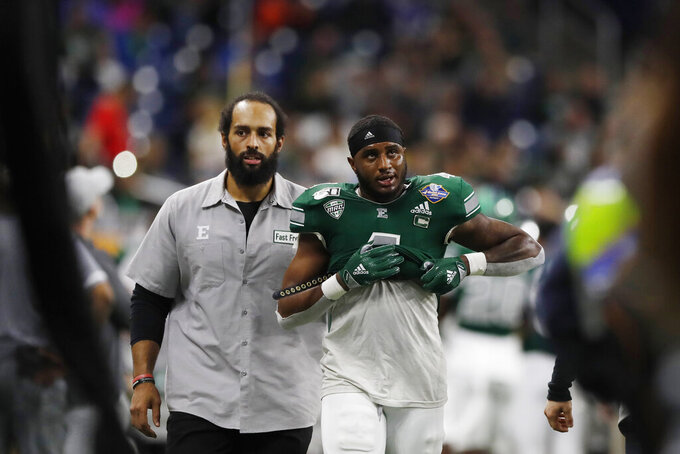 Eastern Michigan defensive back Kevin McGill (4) is escorted to the locker room after being disqualified during the second half of the Quick Lane Bowl NCAA college football game against Pittsburgh, Thursday, Dec. 26, 2019, in Detroit. (AP Photo/Carlos Osorio)