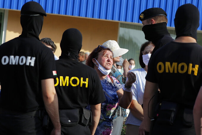 A woman argues with police as they block protesters , to prevent a rally in support opposition candidate Sviatlana Tsikhanouskaya ahead of Sunday's election in Slutsk, Belarus, Tuesday, Aug. 4, 2020. Belarusian police on Tuesday abruptly banned Tsikhanouskaya's previously approved rally in the city of Slutsk, about 100 kilometers (about 60 miles) south of Minsk, under the pretext of road repairs. Officers dispersed several hundred people who had gathered for the rally and detained at least 20 of them, according to Belarusian human rights organization Viasna. (AP Photo/Sergei Grits)