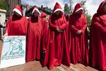 Women dressed like characters from The Handmaid's Tale demonstrate against all government restrictions related to concern about the spread of COVID-19, Saturday, May 30, 2020, outside the Statehouse in Boston. (AP Photo/Michael Dwyer)