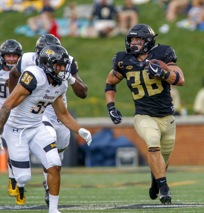 Wake Forest running back Cade Carney, right, carries the football for a first down as Towson defensive back Coby Tippett pursues him in the second half of an NCAA college football game in Winston-Salem, N.C., Saturday, Sept. 8, 2018. (AP Photo/Nell Redmond)