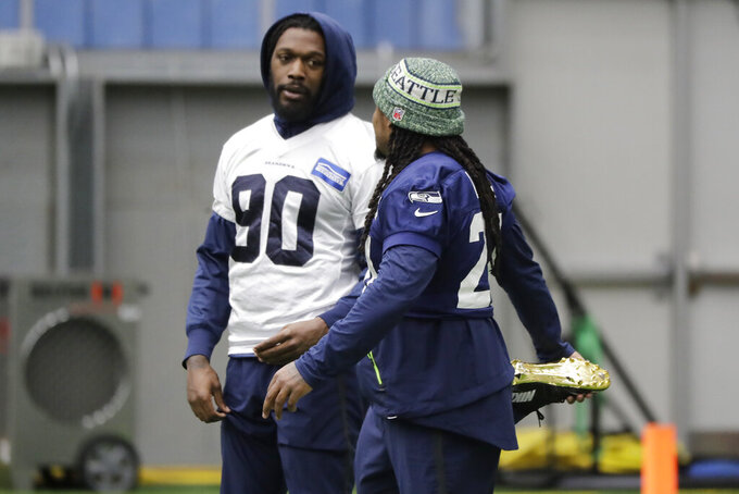 Seattle Seahawks running back Marshawn Lynch, right, stretches as he talks with defensive end Jadeveon Clowney, left, before NFL football practice, Friday, Dec. 27, 2019, in Renton, Wash. (AP Photo/Ted S. Warren)