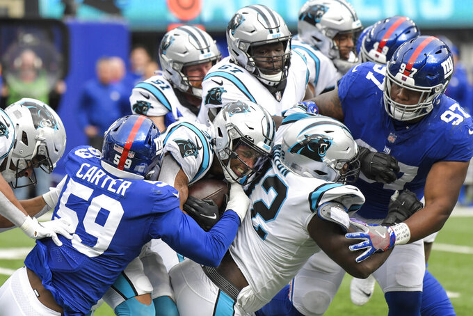 New York Giants' Lorenzo Carter (59) tackles Carolina Panthers running back Chuba Hubbard (30) during the first half of an NFL football game, Sunday, Oct. 24, 2021, in East Rutherford, N.J. (AP Photo/Bill Kostroun)