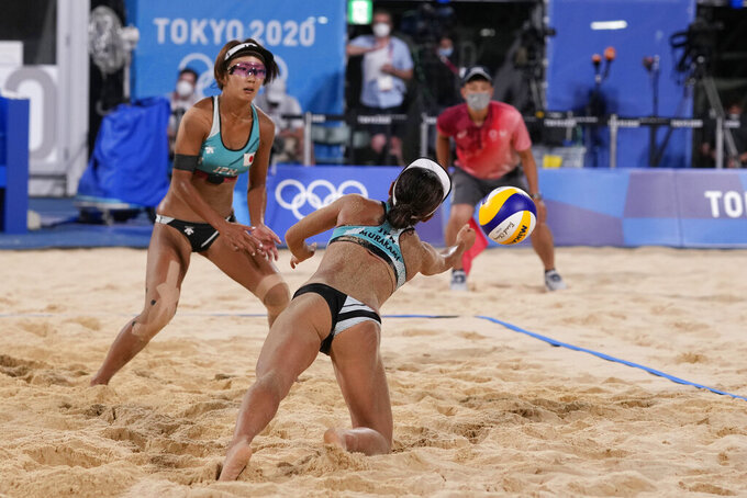 Megumi Murakami, right, of Japan, dives for the ball as teammate Miki Ishii looks on during a women's beach volleyball match against Germany at the 2020 Summer Olympics, Monday, July 26, 2021, in Tokyo, Japan. (AP Photo/Petros Giannakouris)