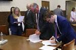 Attorneys for the state look over court documents following Judge Thad Balkman's announcement of his decision in the Opioid Lawsuit in Norman, Okla., Monday, Aug. 26, 2019. Balkman found Johnson & Johnson and its subsidiaries helped fuel the state's opioid drug crisis and ordered the consumer products giant to pay $572 million to help abate the problem in the coming years. (AP Photo/Sue Ogrocki, Pool)
