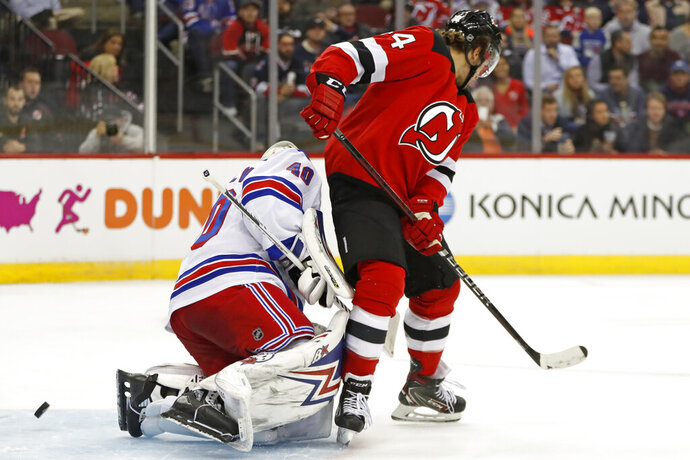 New Jersey Devils left wing Miles Wood (44) scores a goal on New York Rangers goaltender Alexandar Georgiev (40) during the second period of an NHL hockey game Thursday, Oct. 17, 2019, in Newark, N.J. (AP Photo/Kathy Willens)