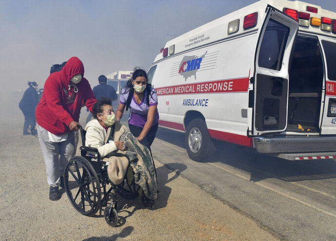 Elderly residents of the Riverside Heights Healthcare Center in Jurupa Valley, Calif., are evacuated from their care facility as flames and smoke from the Hill Fire approach Wednesday Oct 30, 2019. (Will Lester/The Orange County Register via AP)