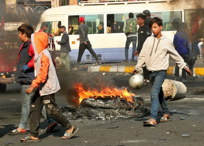 Protesters set fires during ongoing protests in Baghdad, Iraq, Sunday, Dec. 1, 2019. Iraq's parliament approved the resignation of Prime Minister Adel Abdul-Mahdi on Sunday, amid ongoing violence and anti-government demonstrations in the capital. (AP Photo/Hadi Mizban)