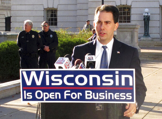 FILE - In this Nov. 3, 2010 file photo, Governor-elect Scott Walker speaks to reporters outside the state Capitol in Madison, Wis. Wisconsin's new Democratic governor is repurposing highway signs that his Republican predecessor installed declaring the state to be