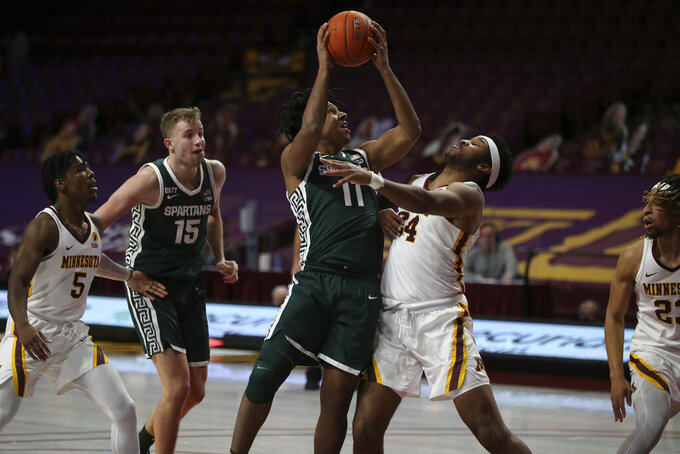 Michigan State's A.J. Hoggard (11) pushes up to the basket against Minnesota's Eric Curry (24) during the second half of an NCAA college basketball game, Monday, Dec. 28, 2020, in Minneapolis. Minnesota won 81-56. (AP Photo/Stacy Bengs)