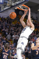 Utah State center Kuba Karwowski (52) dunks the ball as UTSA guard Keaton Wallace (22) and forward Byron Frohnen (3) defend during the first half of an NCAA college basketball game Monday, Nov. 18, 2019, in Logan, Utah. (AP Photo/Eli Lucero)