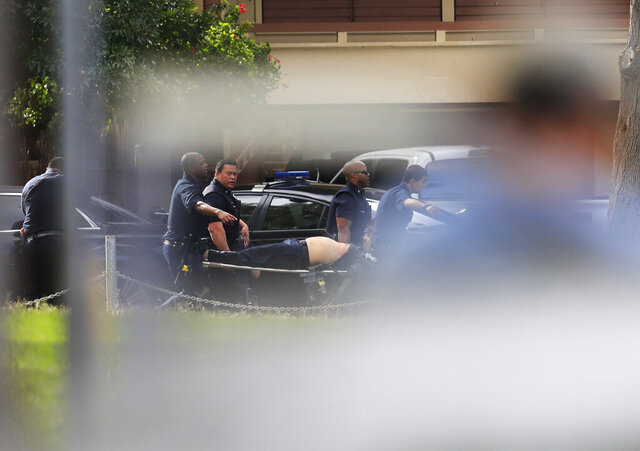 Honolulu police carry an injured officer after a shooting and domestic incident at a residence on Hibiscus Road near Diamond Head on Sunday, Jan. 19, 2020, in Honolulu. Witnesses say at least two Honolulu police officers were shot and two civilians were injured. (Jamm Aquino/Honolulu Star-Advertiser via AP)