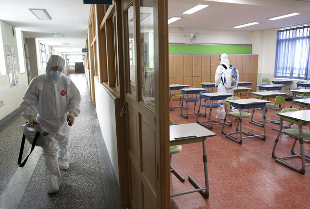 Workers wearing protective gear disinfect as a precaution against the new coronavirus in a class at a high school in Busan, South Korea, Saturday, May 30, 2020. (Jo Jung-ho/Yonhap via AP)