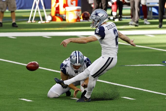 Dallas Cowboys punter Hunter Niswander (1) holds as place kicker Greg Zuerlein (2) kicks a field goal in the first half of an NFL football game against the Washington Football Team in Arlington, Texas, Thursday, Nov. 26, 2020. (AP Photo/Ron Jenkins)