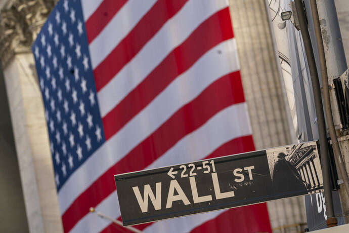 The Wall Street street sign is framed by a giant American flag hanging on the New York Stock Exchange, in a Monday, Sept. 21, 2020 file photo. Stocks are opening higher on Wall Street, recovering after their first four-week losing streak in more than a year. A burst of corporate deals helped give investors confidence to put money back in the market, and the S&P 500 rose 1.4% in the early going Monday, Sept. 28, 2020.  (AP Photo/Mary Altaffer, File)