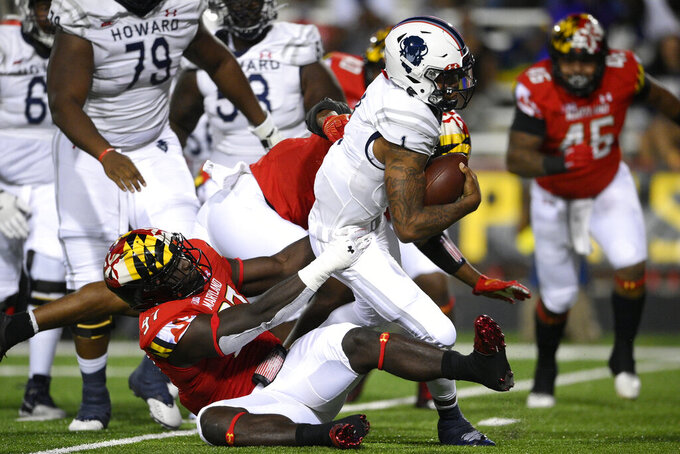 Howard quarterback Undre Lindsay (1) is sacked by Maryland defensive lineman Sam Okuayinonu (97) during the first half of an NCAA college football game, Saturday, Sept. 11, 2021, in College Park, Md. (AP Photo/Nick Wass)