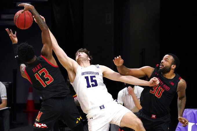Northwestern center Ryan Young, center, battles for a rebound against Maryland guard Hakim Hart, left, and forward Galin Smith during the first half of an NCAA college basketball game in Evanston, Ill., Wednesday, March 3, 2021. (AP Photo/Nam Y. Huh)