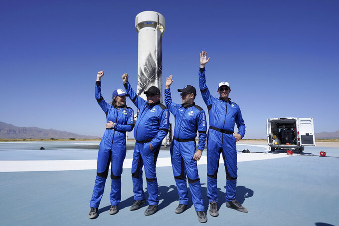 Blue Origin's New Shepard rocket latest space passengers from left, Audrey Powers, William Shatner, Chris Boshuizen, and Glen de Vries raise their hands during a media availability at the spaceport near Van Horn, Texas, Wednesday, Oct. 13, 2021. (AP Photo/LM Otero)