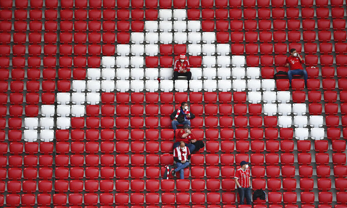 Fans sit on the tribune as they wait the start of the Bundesliga soccer match between Bayern Munich and FC Augsburg at the Allianz Arena stadium in Munich, Germany, Saturday, May 22, 2021. (Sven Hoppe, Pool via AP)