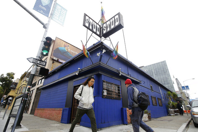 FILE - This July 6, 2016, file photo shows pedestrians walking in front of The Stud bar in San Francisco. The Stud, one of the nation's most celebrated gay bars, is being forced from its home amid the financial fallout of the coronavirus pandemic. (AP Photo/Jeff Chiu, File)