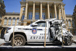 A wrecked Iowa Department of Transportation motor vehicle enforcement vehicle sits on display outside the Iowa Capitol Building in Des Moines during a press conference announcing the Iowa Traffic Fatality Reduction Task Force on Tuesday, June 8, 2021. (Bryon Houlgrave/The Des Moines Register via AP)