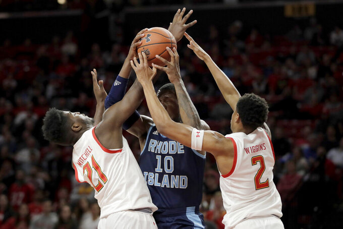 Rhode Island forward Cyril Langevine (10) tries to go up for a basket as Maryland forward Makhi Mitchell (21) and guard Aaron Wiggins (2) defend during the second half of an NCAA college basketball game, Saturday, Nov. 9, 2019, in College Park, Md. Maryland won 73-55. (AP Photo/Julio Cortez)