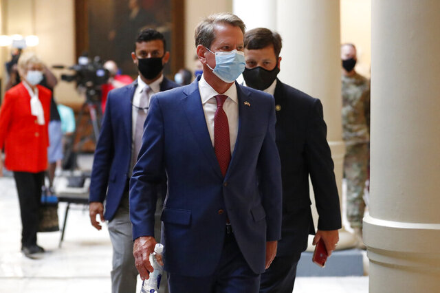Georgia Gov. Brian Kemp returns to his office after giving a coronavirus briefing at the Capitol Friday, July 17, 2020, in Atlanta.  Kemp is suing Atlanta Mayor Keisha Lance Bottoms over its face mask mandate. (AP Photo/John Bazemore)