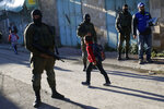 In this Tuesday, Feb. 12, 2019 photo, A Palestinian observers, right, watches as children walk past Israeli soldiers on their way to school in the West Bank city of Hebron. Following Israel's expulsion of an international observer force from this volatile West Bank city, Palestinian activists are trying to fill the void by launching their own patrols to document alleged Israeli settler violence. (AP Photo/Majdi Mohammed)