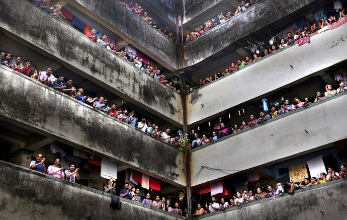 People clap from balconies in show of appreciation to health care workers at a Chawl in Mumbai, India, Sunday, March 22, 2020. India is Sunday observing a 14-hour
