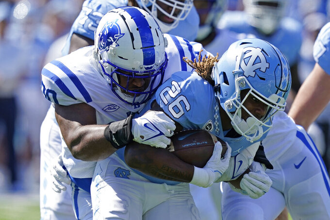 Duke defensive tackle DeWayne Carter, left, tackles North Carolina running back D.J. Jones (26) during the first half of an NCAA college football game in Chapel Hill, N.C., Saturday, Oct. 2, 2021. (AP Photo/Gerry Broome)