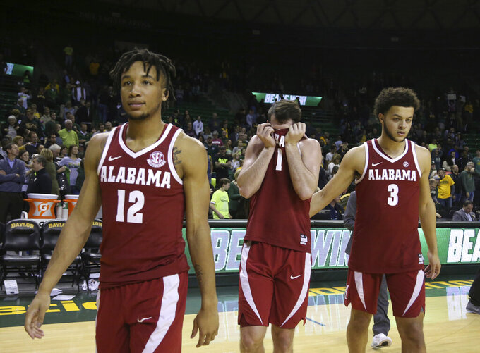 FILE - In this Jan. 26, 2019, file photo, Alabama guard Riley Norris, center, reacts to their loss against Baylor while walking off the court with guard Dazon Ingram, left, and forward Alex Reese, right, following an NCAA college basketball game, in Waco, Texas. Alabama has beaten one Top 5 team and pushed another down to the wire on the road and also suffered some humbling defeats.  That inconsistency has left the Crimson Tide (15-11, 6-7 Southeastern Conference) in a precarious position in the team's bid to make a second straight NCAA Tournament. (Rod Aydelotte/Waco Tribune-Herald via AP, File)