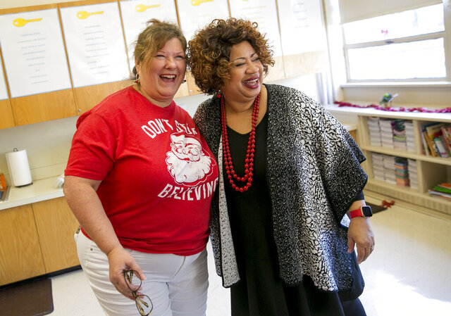 In this Dec. 20, 2019 photo, Karen Gregory, Pre-K 4 teacher, embraces Doreatha White, principal, as she celebrates her last day with staff and students at Berkley Campostella Early Childhood Center in Norfolk, Va. White applied for the Apple partnership in 2015 on a whim. Out of the 114 selected, Berkley-Campostella was the only preschool program. Two years later, when Virginia adopted computer science standards for kindergarten through 12th grade, Berkley-Campostella preschoolers already were coding. (Kristen Zeis/The Virginian-Pilot via AP)
