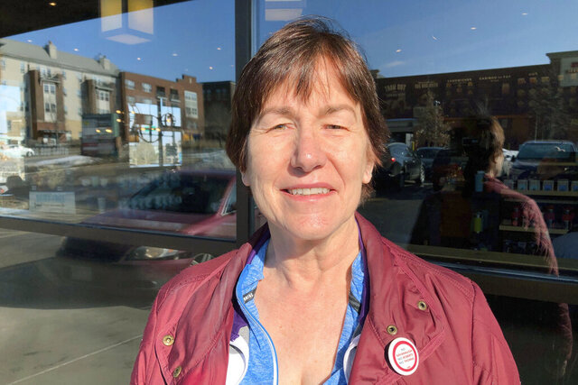 Gail Hayes, 67, a retired child care provider from Burnsville, Minn., discusses the state of the political campaign on Wednesday, March 4, 2020, in Burnsville, a Minneapolis suburb in Dakota County, a once traditionally Republican area that has become swing territory in recent elections. The Democrat, who voted for Joe Biden on Super Tuesday, wore her political sentiments on her lapel, with a button that read,