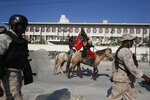 Protesters on horses, one dressed as Haitian revolution leader Jean-Jacques Dessalines, are escorted by police as they ride past the U.S. embassy, during a march demanding the U.S. stay out of Haiti's politics, in Port-au-Prince, Haiti, Thursday, Oct. 17, 2019. Haiti's embattled President Jovenel Moïse was forced on Thursday to hold a private ceremony amid heavy security for what is usually a public celebration of Dessalines, one of the country's founding fathers. (AP Photo/Rebecca Blackwell)