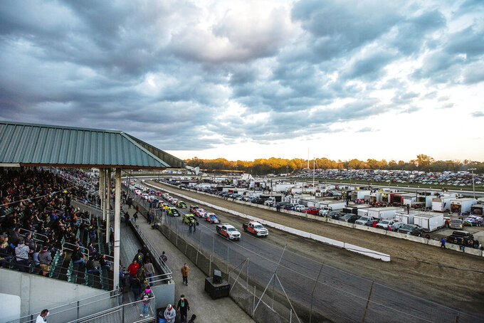In this Oct. 18, 2018, photo, drivers are lined up on the track for the start of the small-block modified feature race during the 57th annual Eastern States Weekend races at the Orange County Fair Speedway in Middletown, N.Y. The track was lengthened to its current distance, 5/8 of a mile, and in 1924 a unique form of clay was trucked in from a pond in nearby Goshen. Annual races were held and regularly attracted 25,000, and after a hiatus for World War II, the stock car was born and the track flourished. It attracted some of the all-time greats, Al Unser, Mario Andretti, and Bobby Allison among them, and capacity crowds. (Kelly Marsh/Times Herald-Record via AP)