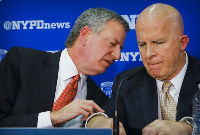 FILE - In this Jan. 30, 2018 file photo, Mayor Bill de Blasio, left, and NYPD police Commissioner James O'Neill confer during a press conference announcing speed-up plans to equip all city police officers and detectives on patrol with body cameras. Multiple reports on Monday, Nov. 4, 2019 say O'Neill, New York City's police commissioner is stepping down after three years leading the nation's largest police department. (AP Photo/Bebeto Matthews, File)