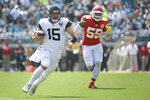 Jacksonville Jaguars quarterback Gardner Minshew III (15) scrambles for yardage past Kansas City Chiefs defensive end Frank Clark (55) during the first half of an NFL football game, Sunday, Sept. 8, 2019, in Jacksonville, Fla. (AP Photo/Phelan M. Ebenhack)