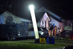 Law enforcement officials respond to the scene of a shooting where officer Christopher Ryan Morton was killed and others wounded as they responded to a 911 call on Tuesday evening, March 6, 2018, in Clinton, Mo. (Keith Myers/The Kansas City Star via AP)