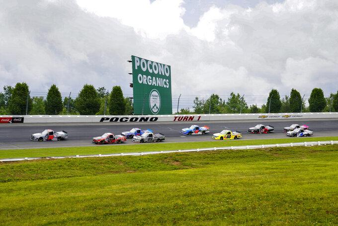 Trucks head through turn one at the start of the NASCAR Truck Series auto race at Pocono Raceway, Saturday, June 26, 2021, in Long Pond, Pa. (AP Photo/Matt Slocum)