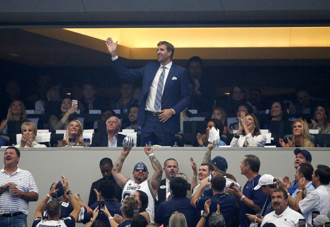 Former Dallas Mavericks player Dirk Nowitzki acknowledges cheers from fans after being introduced in the first half of a NFL football game between the New York Giants and Dallas Cowboys in Arlington, Texas, Sunday, Sept. 8, 2019. (AP Photo/Michael Ainsworth)