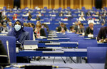 People sit at desks keeping social distance during the general conference of the IAEA, in Vienna, Austria, Monday, Sept. 21, 2020. (AP Photo/Ronald Zak)