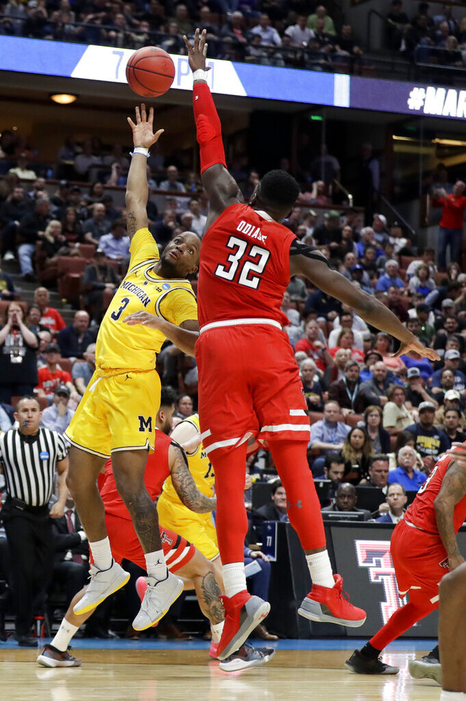 Michigan guard Zavier Simpson shoots over Texas Tech center Norense Odiase during the first half an NCAA men's college basketball tournament West Region semifinal Thursday, March 28, 2019, in Anaheim, Calif. (AP Photo/Marcio Jose Sanchez)