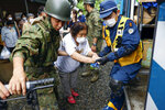 A woman is helped to get into a police vehicle to move from a shelter to another shelter in Kumamura, Kumamoto prefecture, southern Japan Monday, July 6, 2020. Rescue operations continued and rain threatened wider areas of the main island of Kyushu. (Kota Endo/Kyodo News via AP)