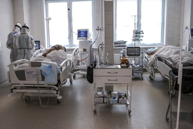 In this photo taken on Saturday, May 2, 2020, doctors attend to a patient inside the intensive care unit for people infected with the new coronavirus, at a hospital in Moscow, Russia.  A Russian epidemiologist says the sharp increase in coronavirus infection cases recorded over the past week reflects increased testing.  Russia on Sunday reported more then ten thousand new cases, nearly double the new cases reported a week ago and the first time the daily tally went into five digits.(AP Photo/Sophia Sandurskaya)