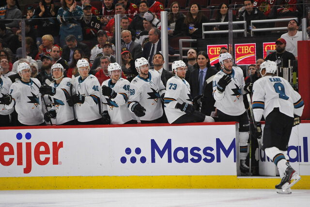 FILE - In this March 11, 2020, file photo, San Jose Sharks' Evander Kane (9) celebrates with teammates on the bench after scoring a goal during the first period of an NHL hockey game against the Chicago Blackhawks in Chicago. The Sharks had started planning for next season long before the news became official that they would be one of the seven teams left home if the NHL resumes its season. (AP Photo/Paul Beaty, File)