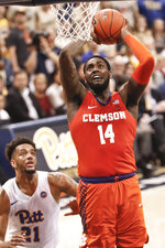 Clemson's Elijah Thomas (14) goes up for a dunk in front of Pittsburgh's Terrell Brown (21) during the second half of an NCAA college basketball game, Wednesday, Feb. 27, 2019, in Pittsburgh. (AP Photo/Keith Srakocic)