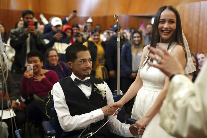 In this Wednesday, Nov. 27, 2019 photo,  Javier Rodriguez and Crystal Cuevas Rodriguez and Crystal Cuevas exchange vows during their wedding before family, friends and medical staff in the chapel at the University of Chicago Medical Center for Care and Discovery in Chicago. Rodriguez, 23, who received two heart transplants as a teenager died in hospice care, days after he married his high school sweetheart, his new bride said.  (Brian Cassella/Chicago Tribune via AP)