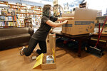 In this Thursday, June 25, 2020, photo, Cat Bock packs items for shipping to a customer from Parnassus Books in Nashville, Tenn. The retail floor of the independent bookstore has essentially become a distribution center since it is closed to customers during the coronavirus pandemic. (AP Photo/Mark Humphrey)