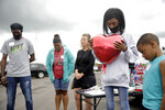 In this Tuesday, May 26, 2020, photo a group of people pray as the arrive to be part of a search party for Miracle Crook, 3, and Tony Crook, 2, at the Shoreline Lakeside Apartments in Tulsa, Okla. At right with balloon is Shantell Chappell and her nephew Kashton Chappell, 6. Searchers used sonar on Tuesday to examine a Tulsa pond for the two young children last seen days ago with their noncustodial mother, who was arrested after being questioned about their disappearance. (Mike Simons/Tulsa World via AP)