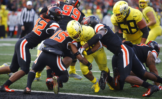 Oregon running back C.J. Verdell, center, bulls his way past Oregon State's Doug Taumoelau (42), Jeffrey Manning Jr. (15) and Hamilcar Rashed Jr (right) for a touchdown in the first half of an NCAA football game in Corvallis, Ore., on Friday, Nov. 23, 2018. (AP Photo/Timothy J. Gonzalez)